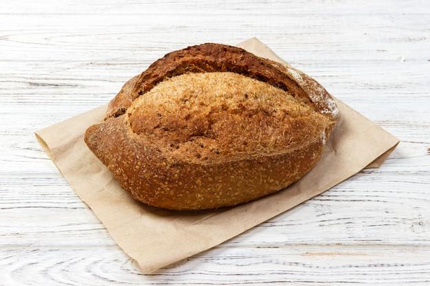 Hogaza de pan de trigo recién horneado en mesa de madera vieja