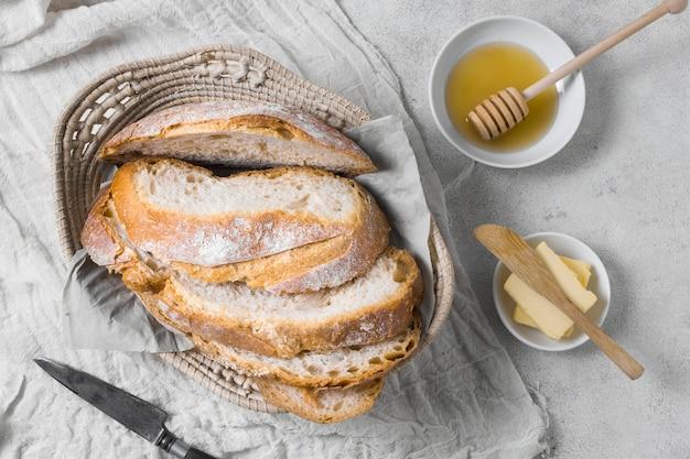 Hogazas de pan en una canasta con mantequilla y miel