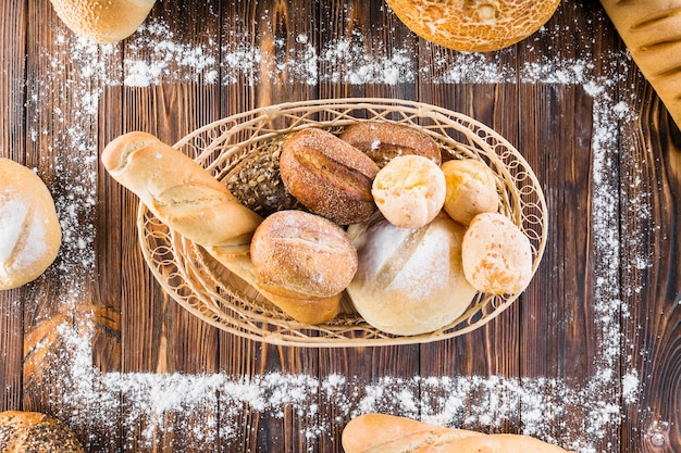 Hogazas de pan en la cesta dentro del marco rectangular hecho con harina