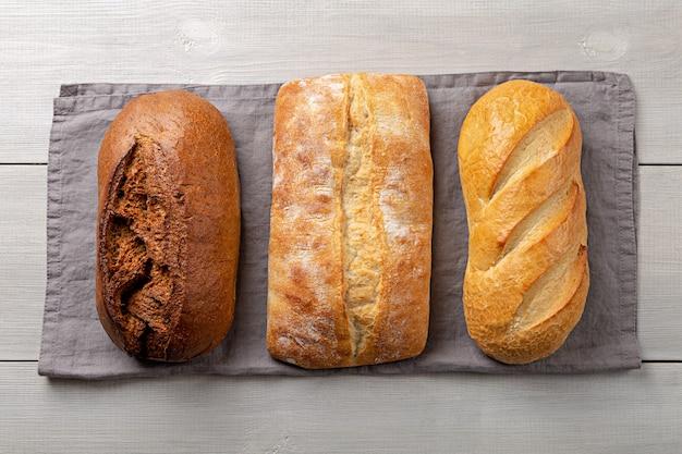 Hogazas de pan integral casero fresco en una servilleta gris sentar planas