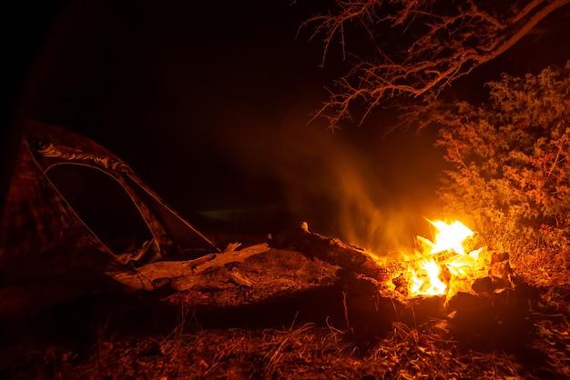 Hoguera brillante cerca de la carpa por la noche en un campamento turístico