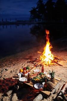 Hoguera y cena servida en la playa.