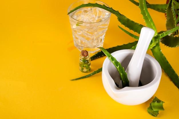 Hoja de aloe vera, mortero blanco lleno de aloe picado y botellas de gel o infusión de aloe.