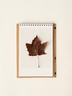 Hoja de arce roja en un cuaderno de página abierta.