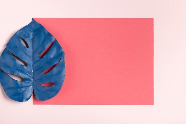 Hoja azul sobre maqueta de fondo rosa
