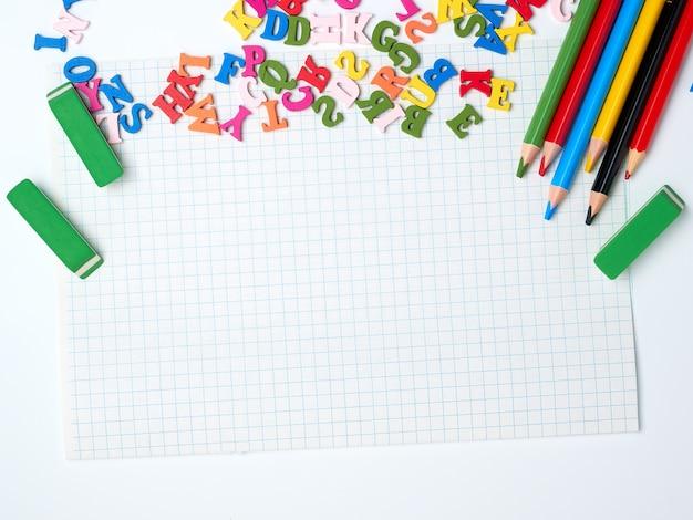 Hoja blanca en blanco de papeles cuadrados y útiles escolares