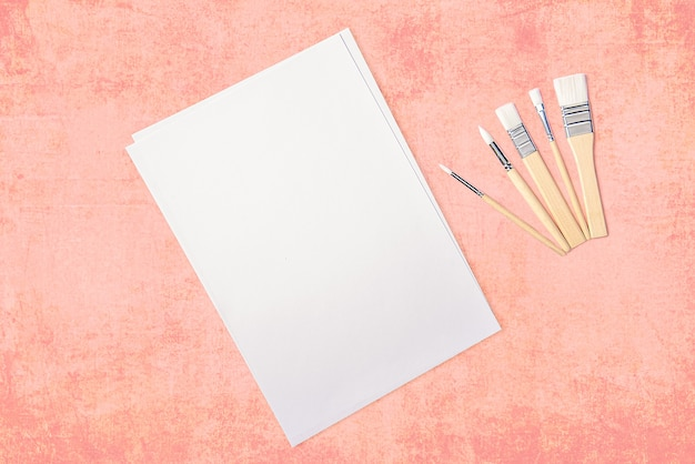 Una hoja blanca limpia y pinceles sobre un fondo rosa texturizado con espacio para copiar.
