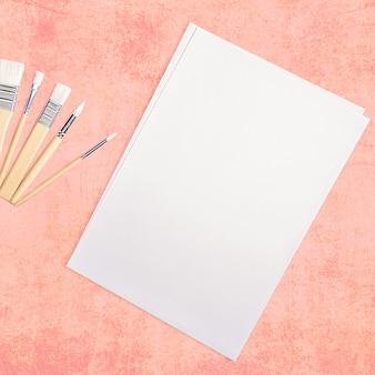 Una hoja blanca limpia y pinceles sobre una superficie rosa texturizada con espacio para copiar.