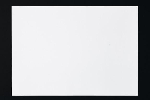 Hoja blanca de papel rectangular sobre un fondo negro minimalismo plano lay