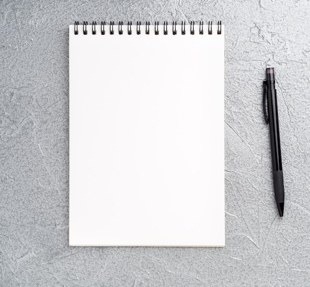 Hoja en blanco del cuaderno con una espiral en un fondo metálico plateado gris neutro con textura
