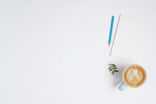 Hoja en blanco; lápiz de color azul y una taza de café capuchino sobre fondo blanco
