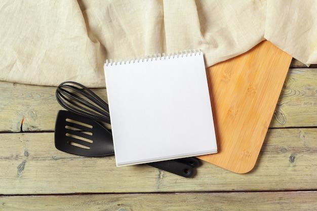 Hoja en blanco de libreta abierta y utensilios de cocina en la mesa con mantel