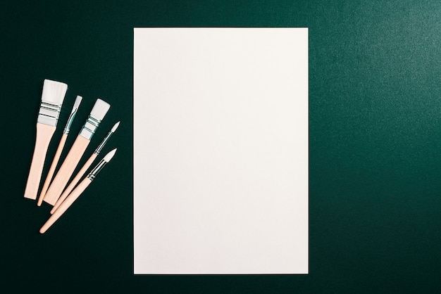 Una hoja en blanco limpio y pinceles sobre un fondo verde oscuro con espacio para copiar. maqueta, maqueta, diseño.