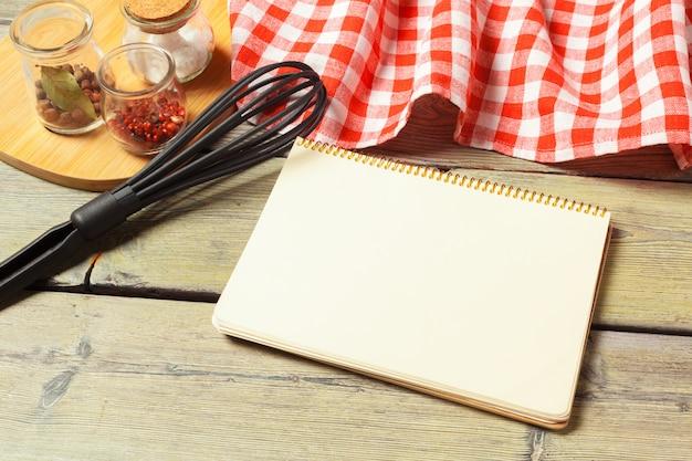 Hoja en blanco de los utensilios abiertos de la libreta y de la cocina en la tabla con el mantel, espacio de la copia