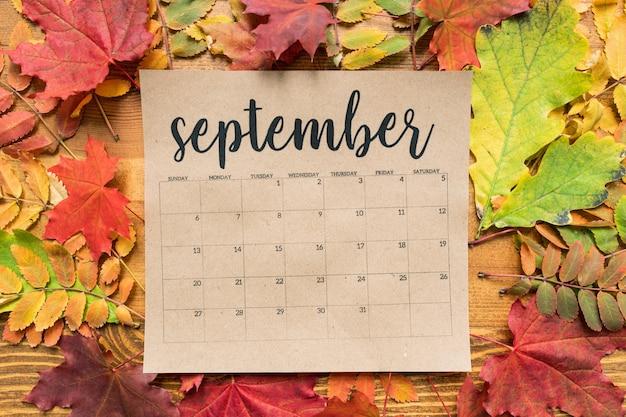 Hoja de calendario de septiembre con múltiples hojas de otoño de color rojo, amarillo y verde