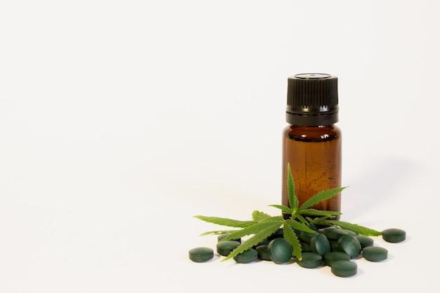 Hoja de cáñamo verde, pastillas y extracto de aceite