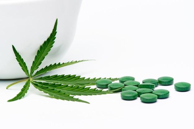 Hoja de cannabis con pastillas y mortero sobre un espacio en blanco.