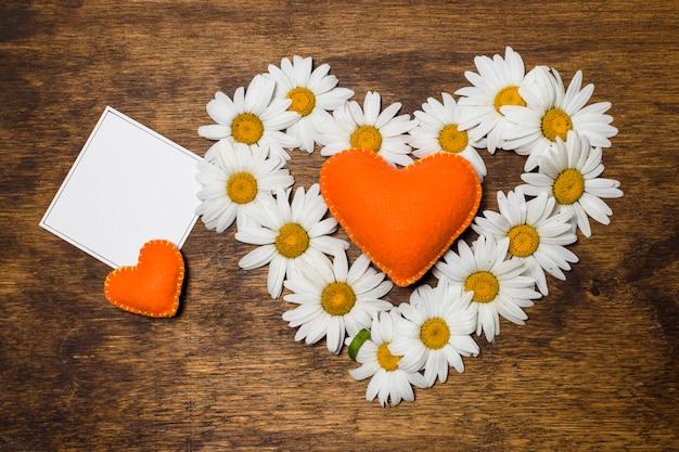 Hoja cerca del corazón ornamental de flores blancas y juguetes naranjas.