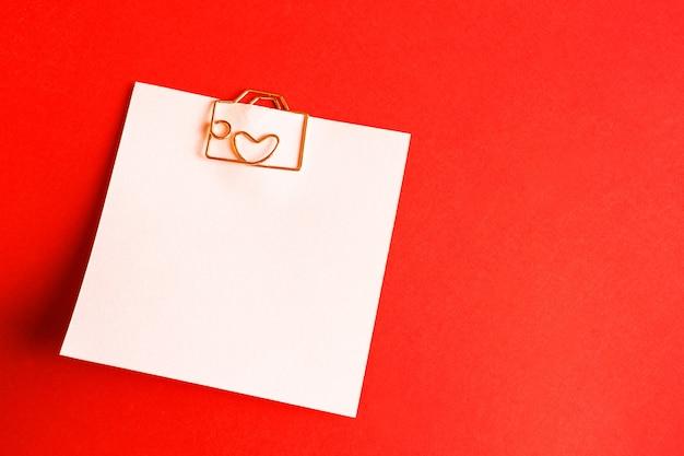 Hoja cuadrada para notas con clip en forma de letra y corazón