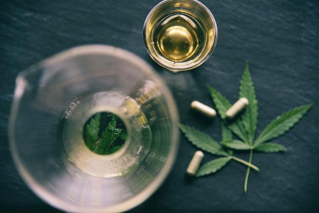 Hoja de marihuana, cannabis, infusiones y cápsulas en la oscuridad.