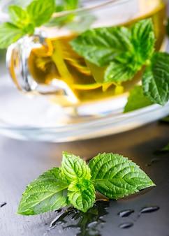 Hoja de menta. hojas de menta. té. té de menta. té de hierbas. té en una taza de vidrio, hojas de menta, té seco, rodajas de limón. té de hierbas y hojas de menta en una placa de pizarra en un restaurante o salón de té.