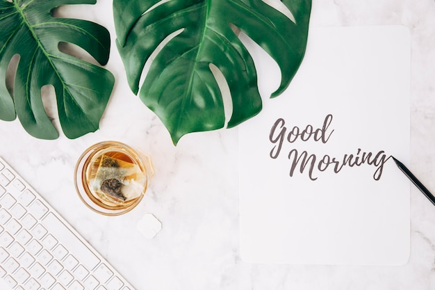 Hoja de monstera; bolsita de té en vidrio transparente; teclado y texto escrito a mano de buena mañana en papel sobre el fondo texturizado.