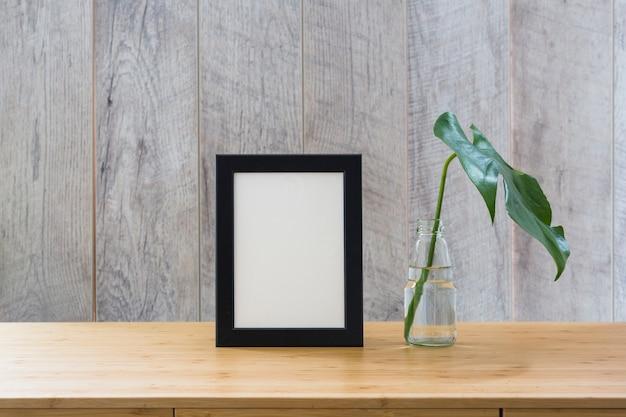 Hoja de monstera en botella de vidrio y marco de fotos en mesa de madera