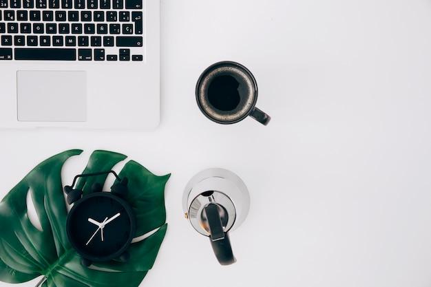 Hoja de monstruo en el reloj de alarma; tetera; taza de café y portátil sobre fondo blanco