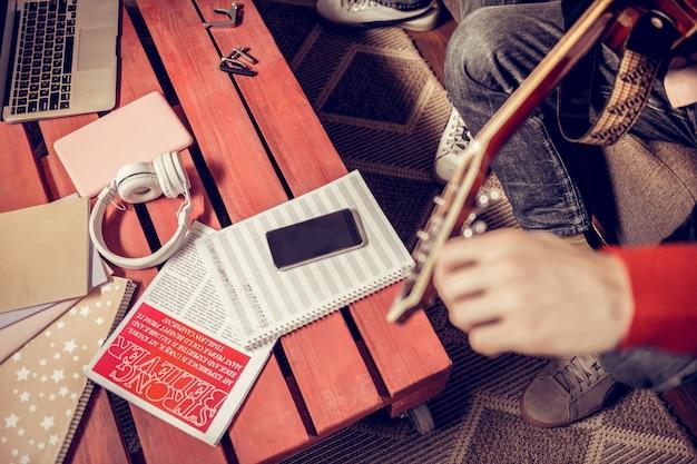 Hoja de notas. músicos sentados en la mesa con una hoja de notas musicales y un teléfono y componiendo una nueva melodía