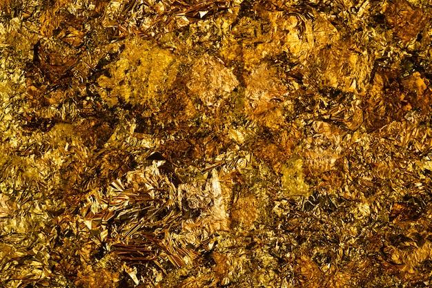 Hoja de oro amarillo brillante o retazos de lámina de oro.