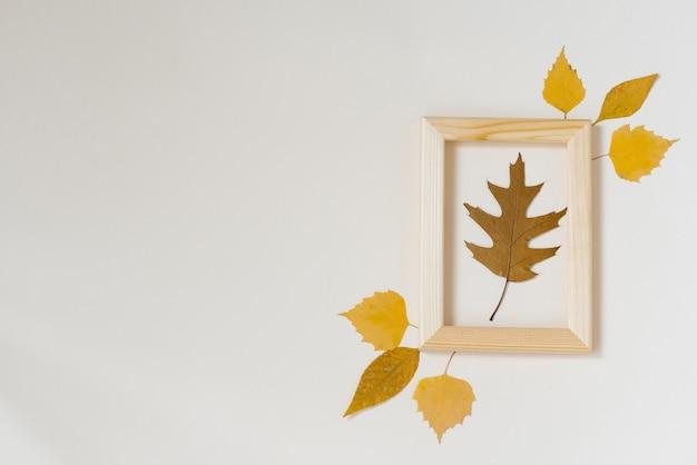 Hoja de otoño caído roble marrón en un marco de madera con hojas amarillas alrededor