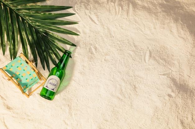 Hoja de palmera botella de bebida y pequeña tumbona en la arena