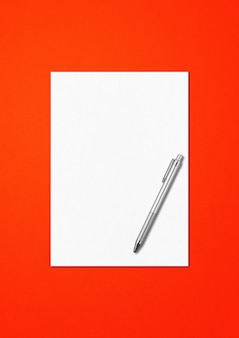 Hoja de papel a4 en blanco y plantilla de maqueta de bolígrafo aislada sobre fondo rojo