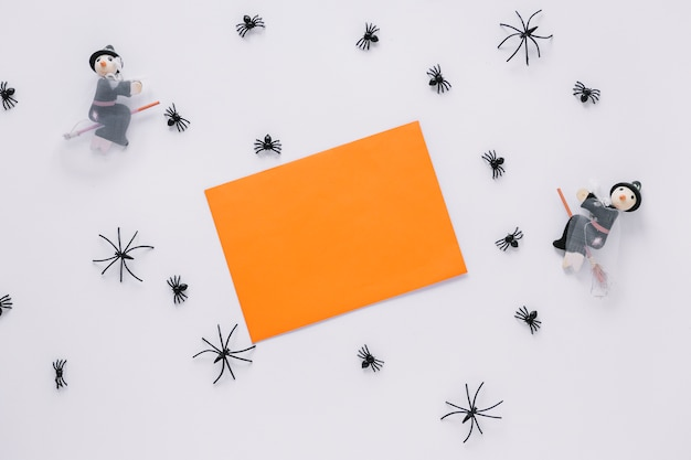 Hoja de papel con arañas decorativas y brujas alrededor
