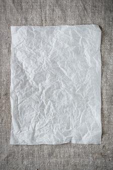 Hoja de papel arrugada en un fondo gris.