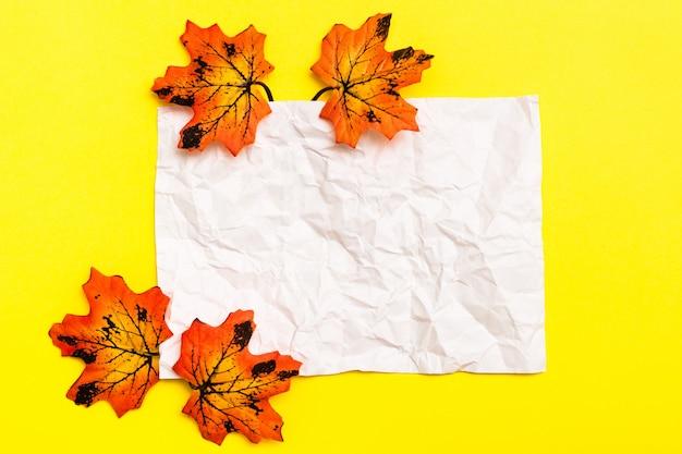 Hoja de papel arrugado en blanco blanco enmarcado por hojas de arce otoñal sobre un fondo de cartón amarillo. copia espacio vista superior