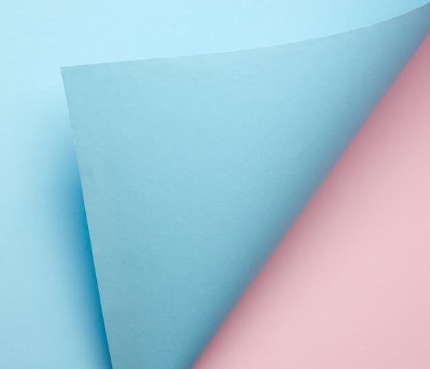 Hoja de papel azul rizado sobre fondo rosa