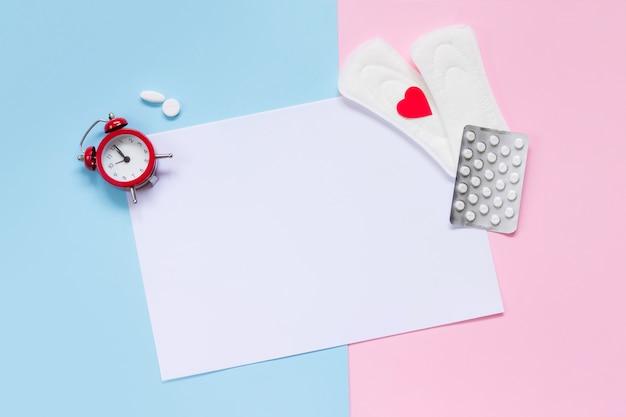 Hoja de papel blanca con almohadillas, reloj despertador, píldoras anticonceptivas hormonales.