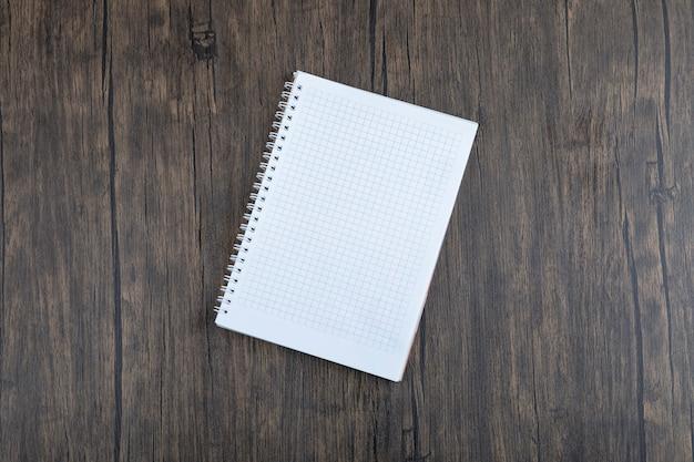 Hoja de papel blanca vacía colocada sobre la mesa de madera.