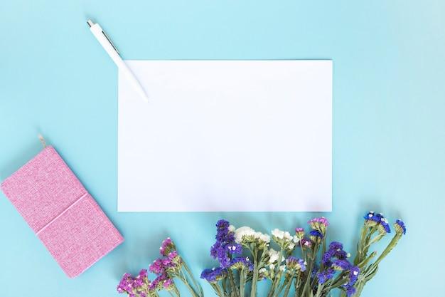 Hoja de papel en blanco; bolígrafo; diario y ramo de flores sobre fondo azul