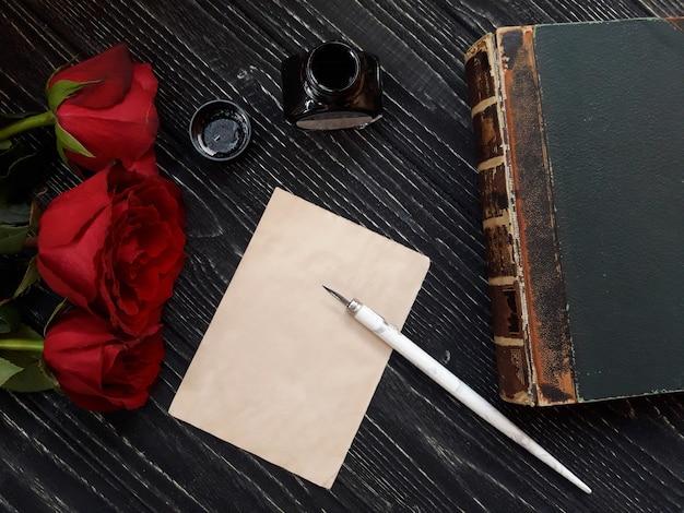 Hoja de papel en blanco con bolígrafo, tintero, libro antiguo y tres rosas rojas
