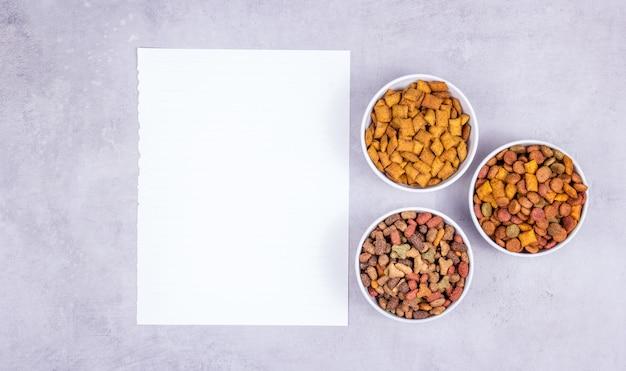 Hoja de papel en blanco y comida seca, espacio de copia