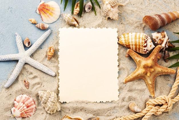 Hoja de papel en blanco con conchas y estrellas de mar en arena