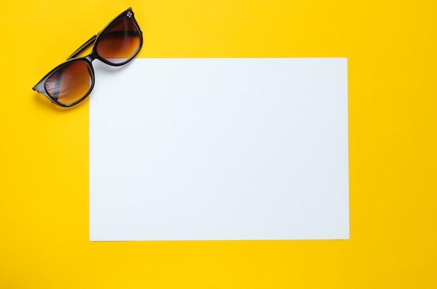 Hoja de papel blanco para espacio de copia, gafas de sol en mesa amarilla. mesa creativa de verano