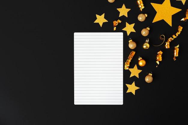 Hoja de papel en blanco con estrellas decorativas doradas.