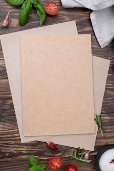 Hoja de papel en blanco con ingredientes para cocinar en la mesa