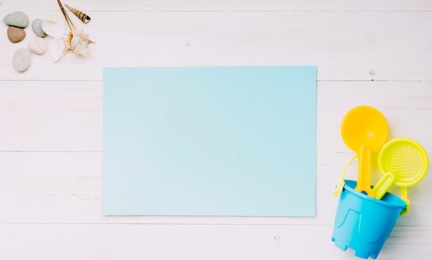Hoja de papel en blanco con objetos de playa sobre fondo claro