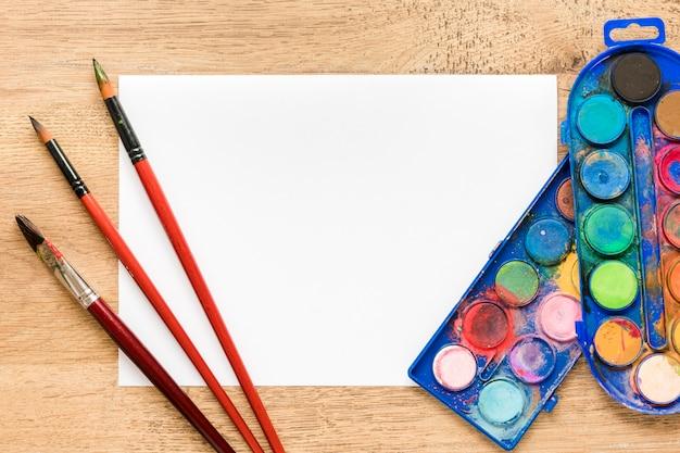 Hoja de papel en blanco con paleta y pinceles