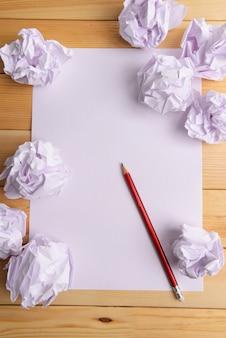 Hoja de papel blanco con papel arrugado y lápiz en primer plano de la mesa