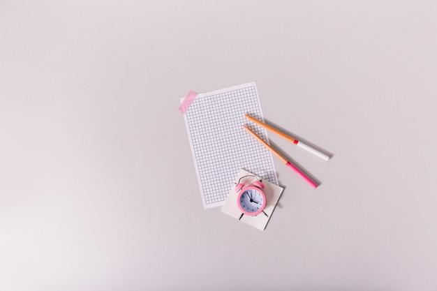 Hoja de papel en blanco pegada con cinta rosa a la mesa